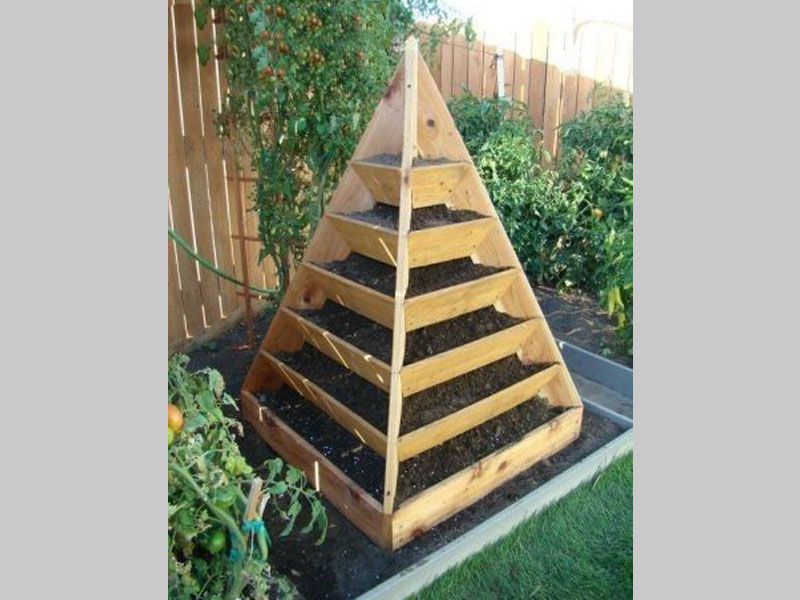 This pyramid garden made of wood is both an art piece as well as an excellent space conserving planter for flowering plants and vegetables. This planter is at home both as a central lawn piece and as a kitchen garden planter.
